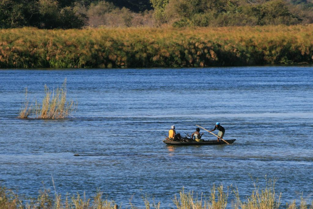 Villagers on the Chobe River in a Makoro, a wooden canoe-like craft.