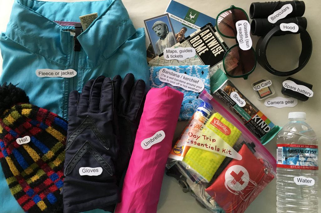 A display of all of the items listed on the one day trip packing list that you might take depending on the weather.