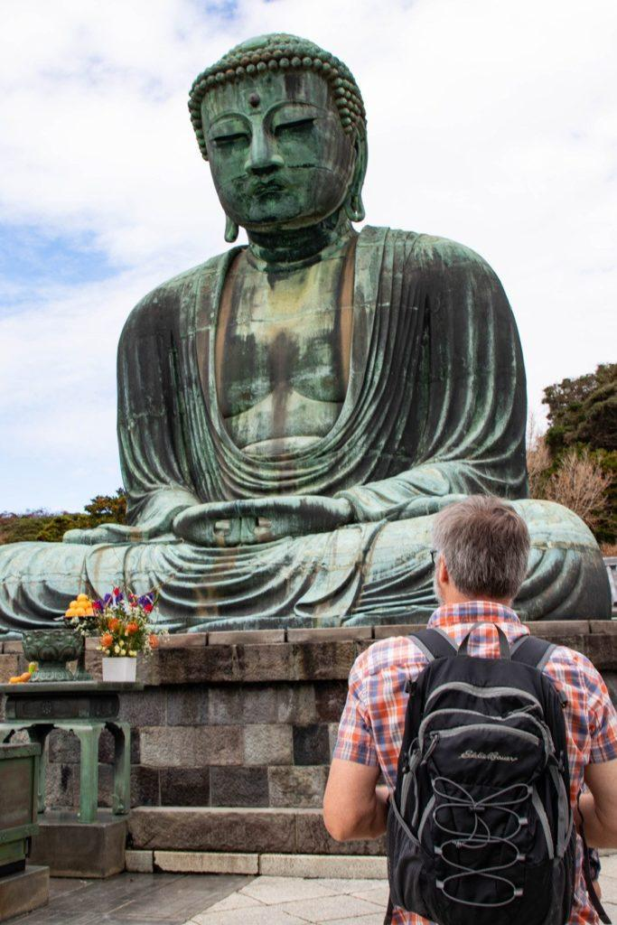 A day tripper with a day trip bag on his back standing before the Great Buddha in Kamakura.