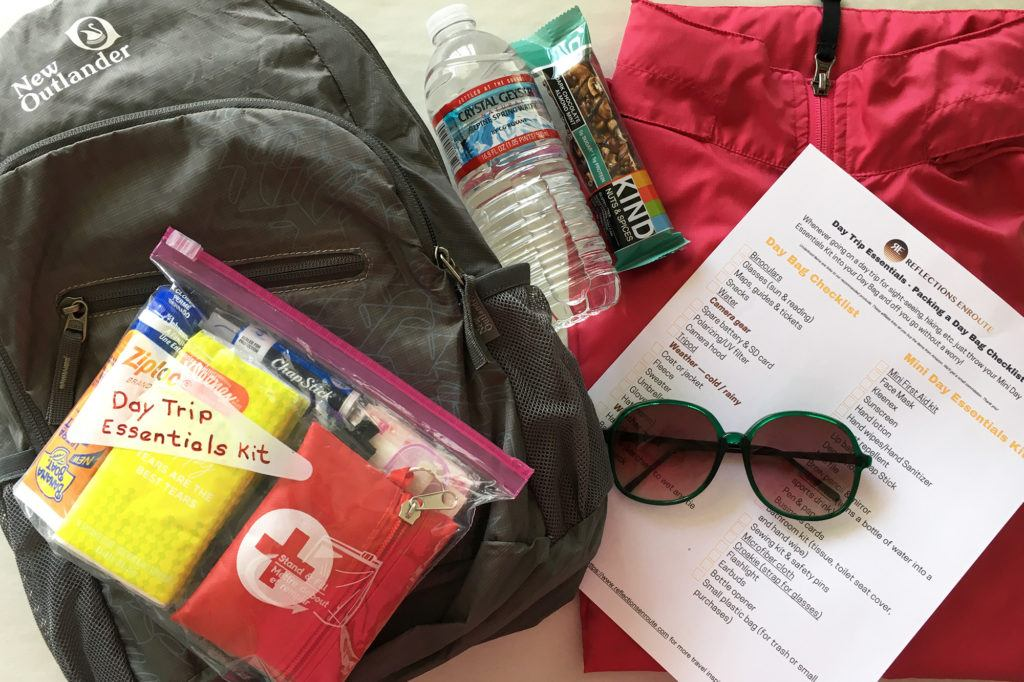 A small day bag with the mini day trip essentials kit, a copy of out day trip check list, and a few typical day bag items.