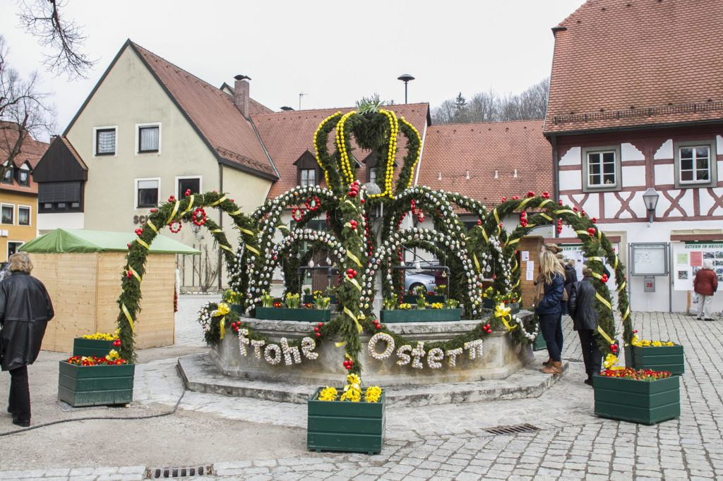 Frohe Ostern, or Happy Easter. People marveling at the intricate design of this Osterbrunnen.