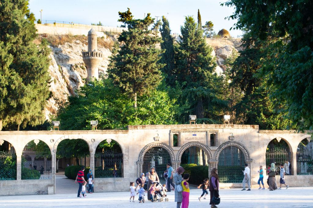 Tourists and locals walking and talking near the Urfa Kale.