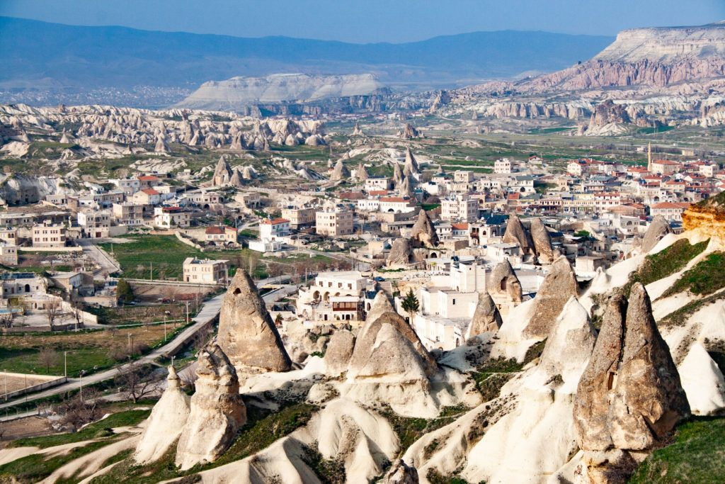 The beautiful town of Goreme, the center of Capadocia, is a mix of white buildings with red roofs and volcanic pillars.