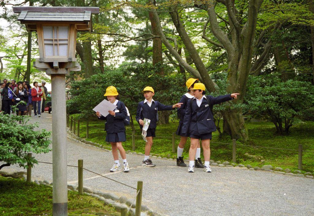 Japanese school children following a map.