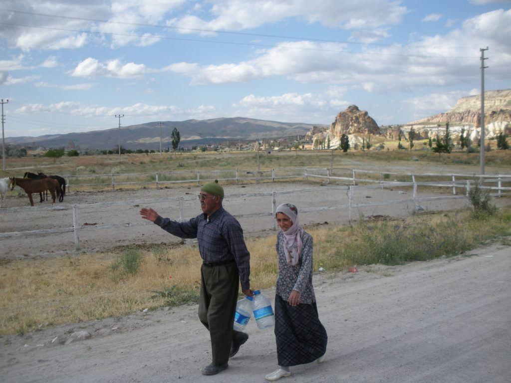 A man and woman carrying water jugs walk along a road in Cappadoccia.
