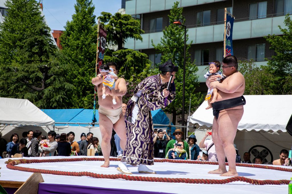 Sumo wrestlers, babies, and referee during the nakizumo competition, a spring festival in Japan.