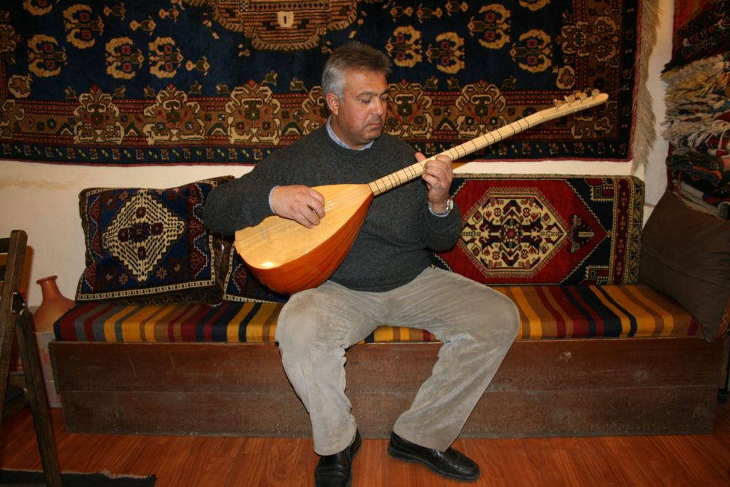 A rug merchant plays a Turkish stringed instrument called a saz or Baglama.