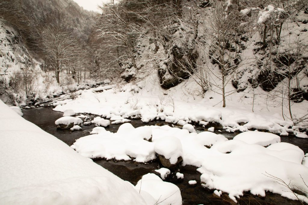 Snow piled high on the rocks in the Shiro River, Japan.