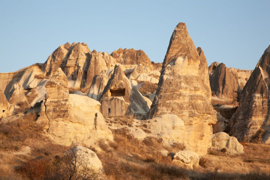 Dwellings carved into stone pillars glow in the late afternoon light.