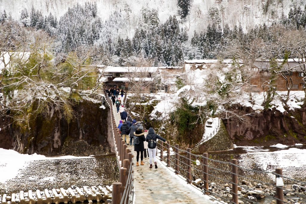 In winter, tourists carefully cross the Shiro River suspension bridge into the village of Ogimachi.
