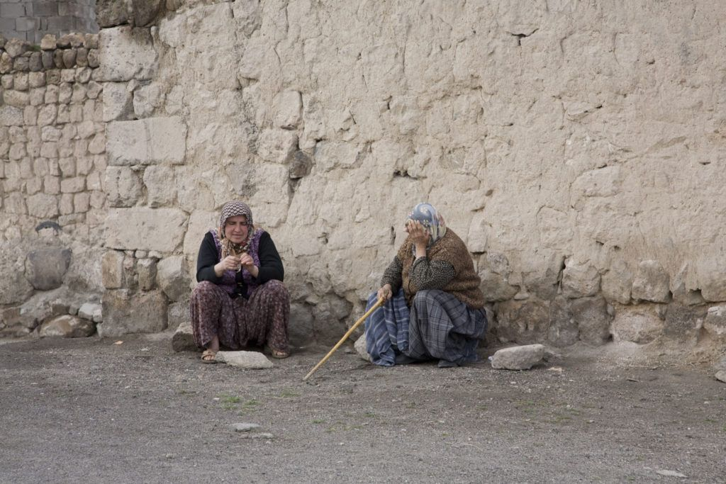 Two women sitting beside a stone wall in Cappadocia, located in central Turkey.
