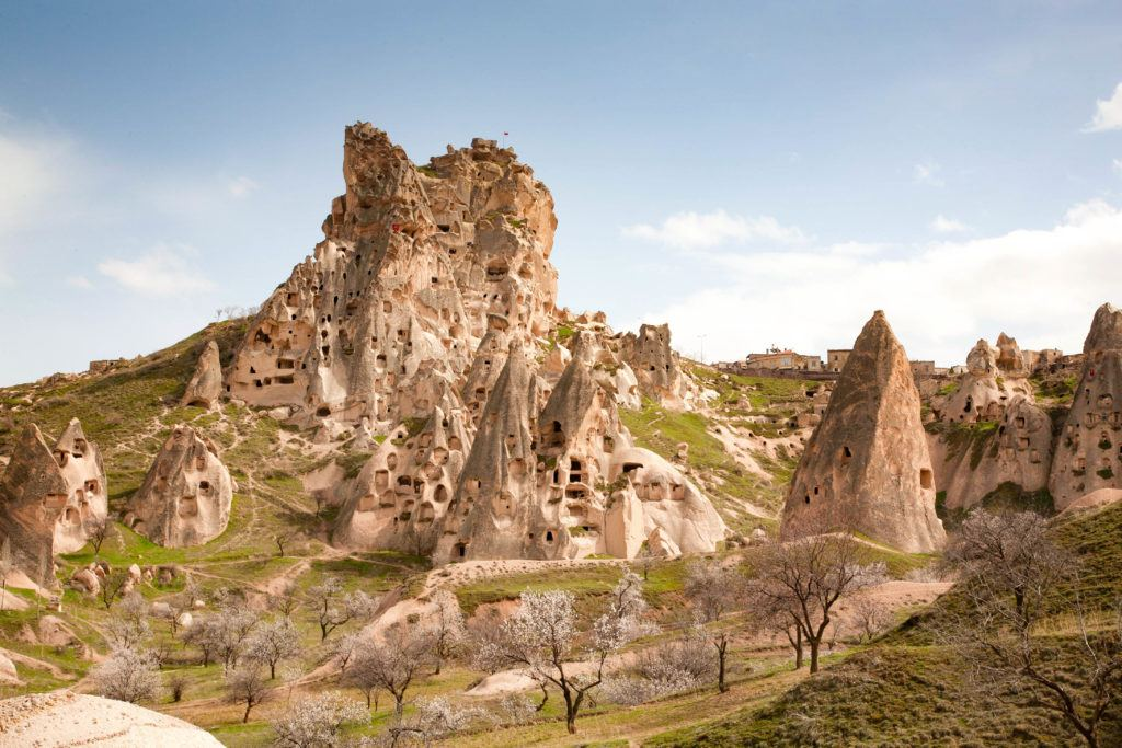 Cluster of cave houses on a beautiful spring day with grass turning green and trees starting to bloom.