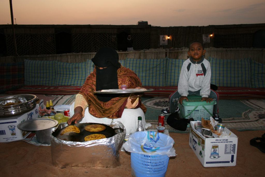 Trying homecooked flatbreads from this woman and her son at the Desert Night Tour.