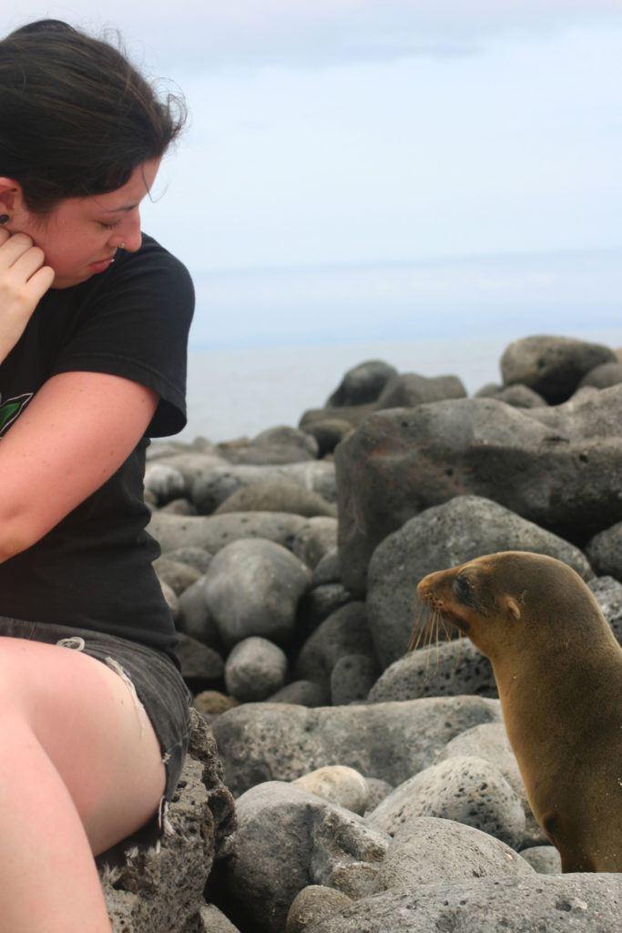 A sea lion walks by Erika on a Galapagos beach.