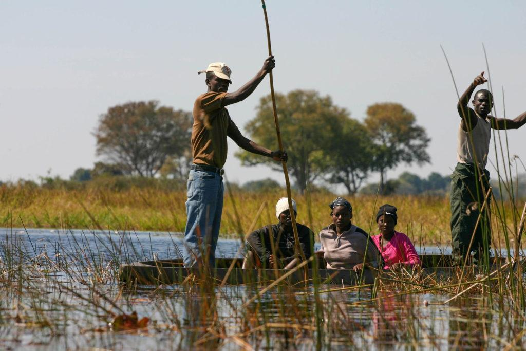 A group of locals poling in the Okavango Delta, a UNESCO World Heritage Site.