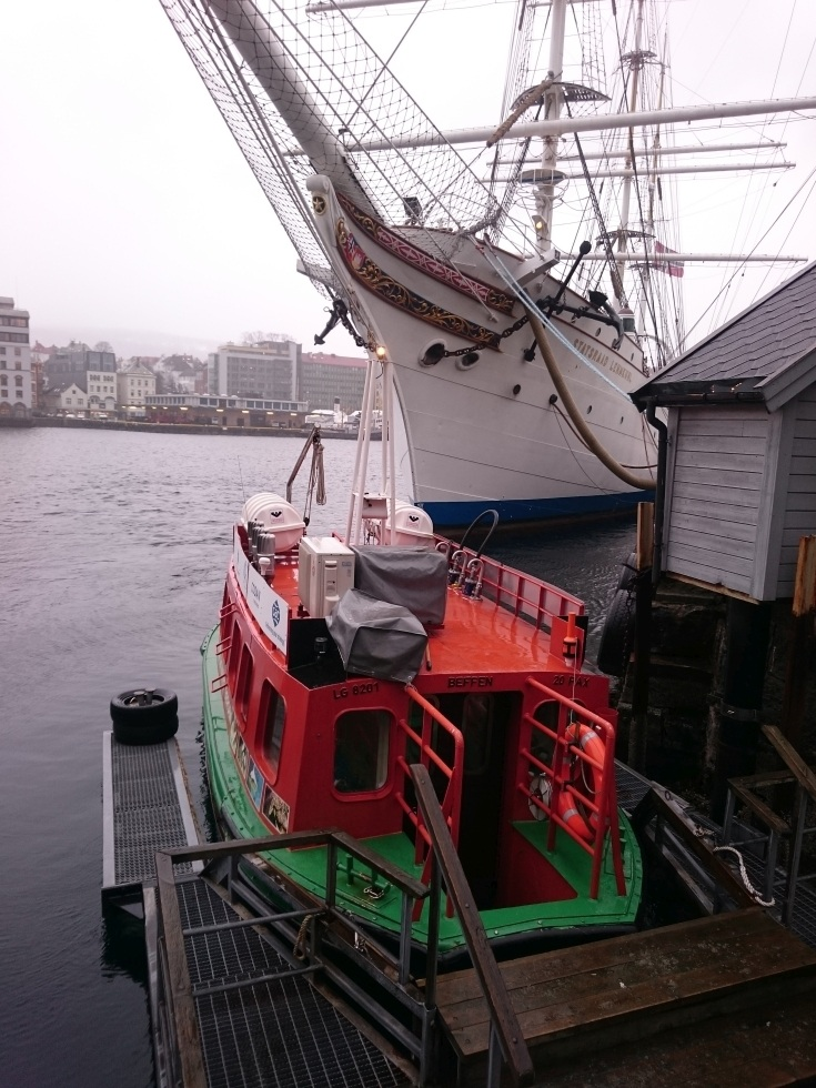 To get around Bergen, take the little green and orange boat dwarfed here by a tall ship across the Bergen harbor.
