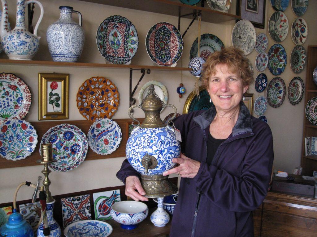 Women holding an Iznik-ceramic tea samovar in a Turkish ceramics shop.