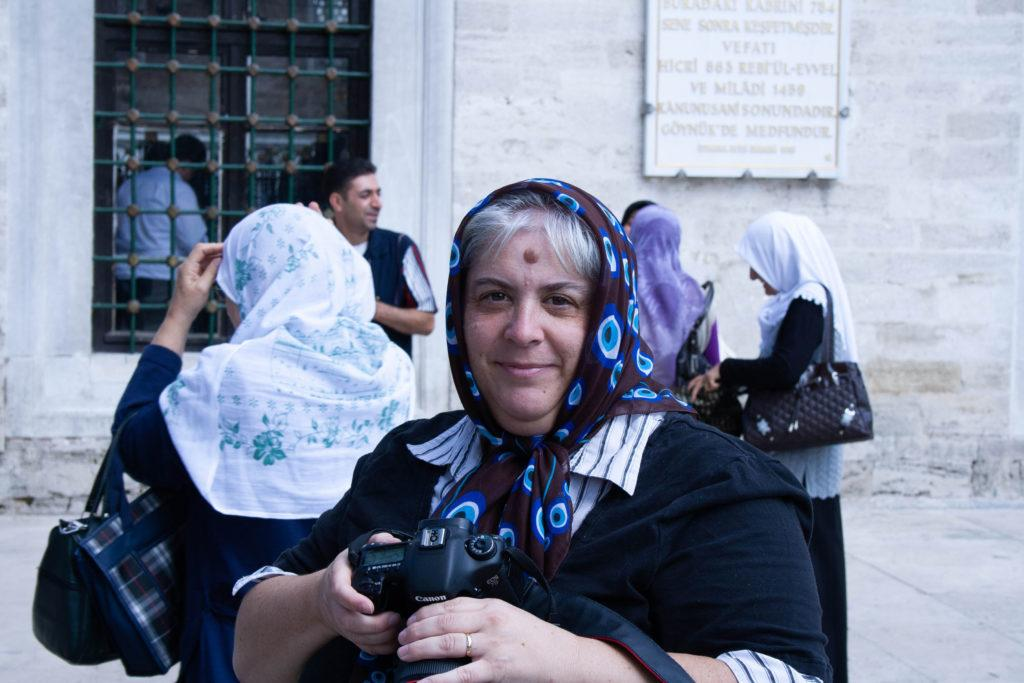 Women with camera in Istanbul wearing a Turkish evil eye scarf.