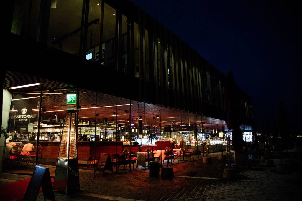 A restaurant at the Bergen Fish Market lit up at night.