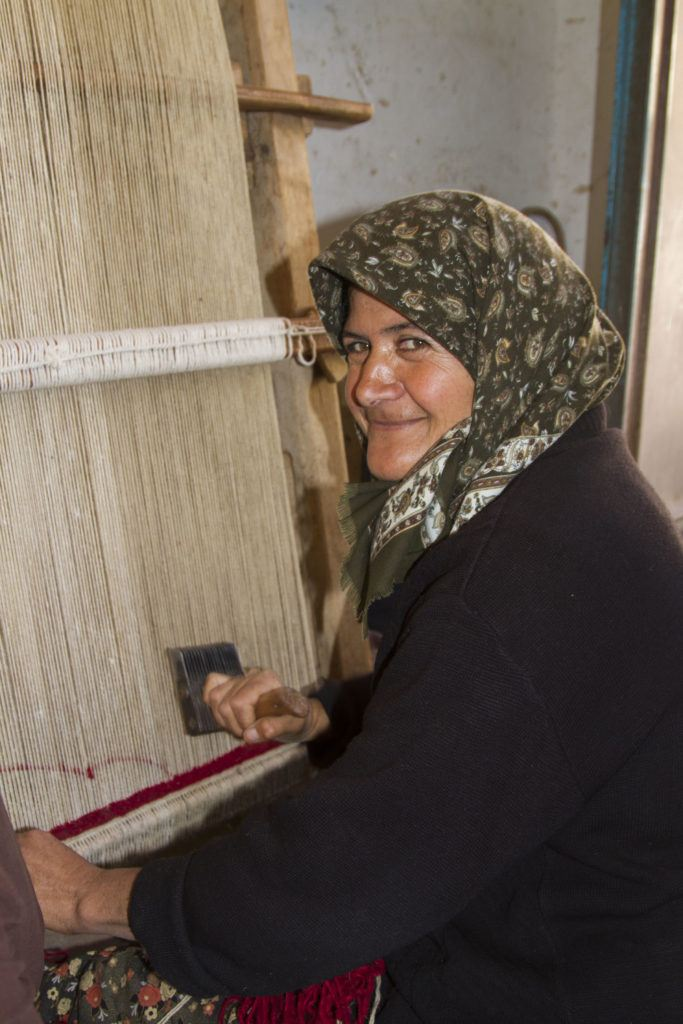 This village woman spends her days knotting rugs.
