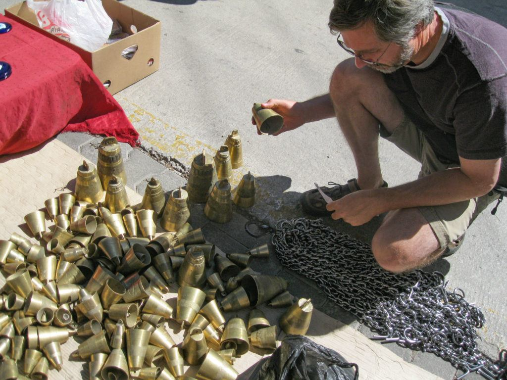 A man looks for just the right Turkish souvenir in a pile of livestock bells.