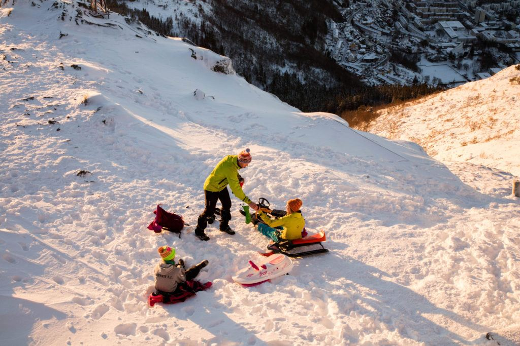 A family sledding in the afternoon light. It's a popular winter activity in Bergen.