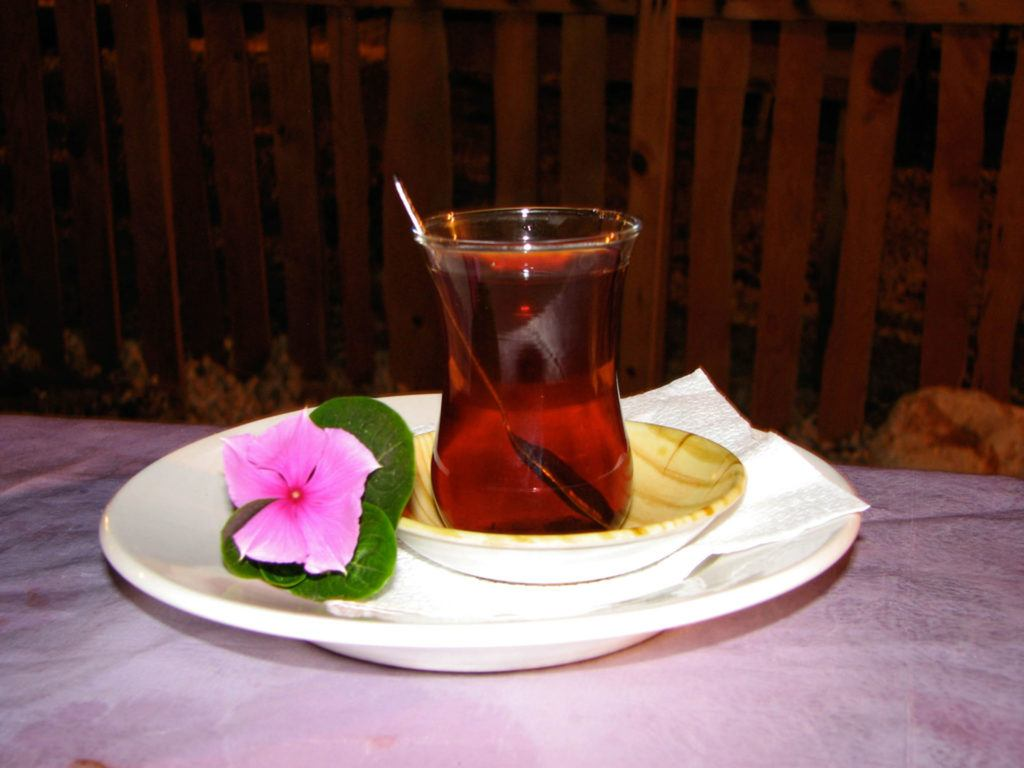 A glass of Turkish tea is elegantly served on a saucer with a pink flower.