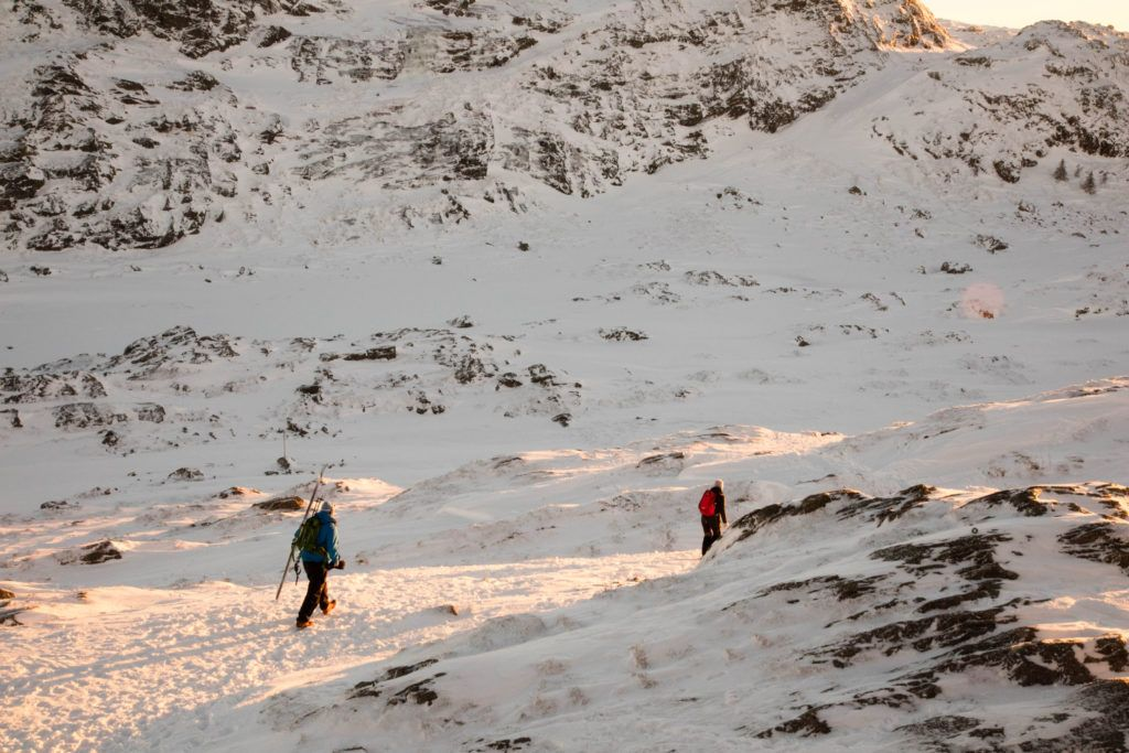 People hiking on a snow-covered trail in winter in Bergen where popular activities include skiing, snow-hiking, and sledding.